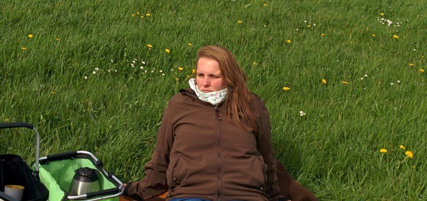 Picknick am Deich, Anna sitzt auf der Decke und trinkt Kaffee.
